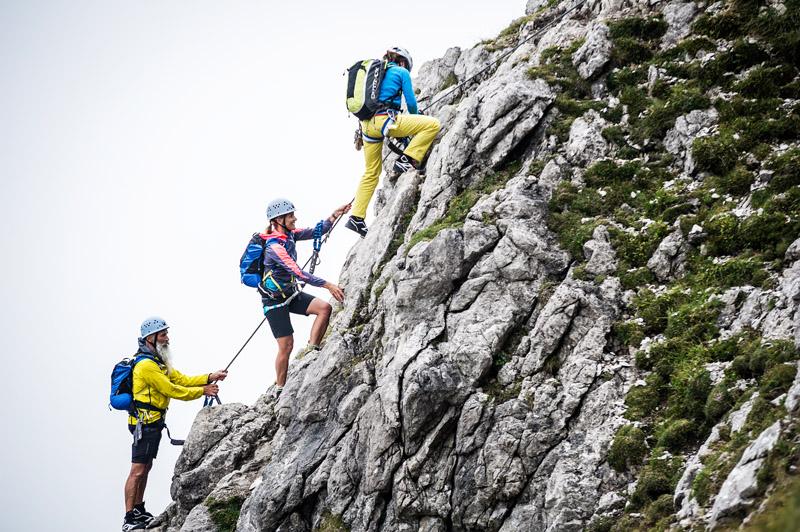 Gekonnt arbeitet sich der Kletterer am Seil nach oben am Klettersteig.