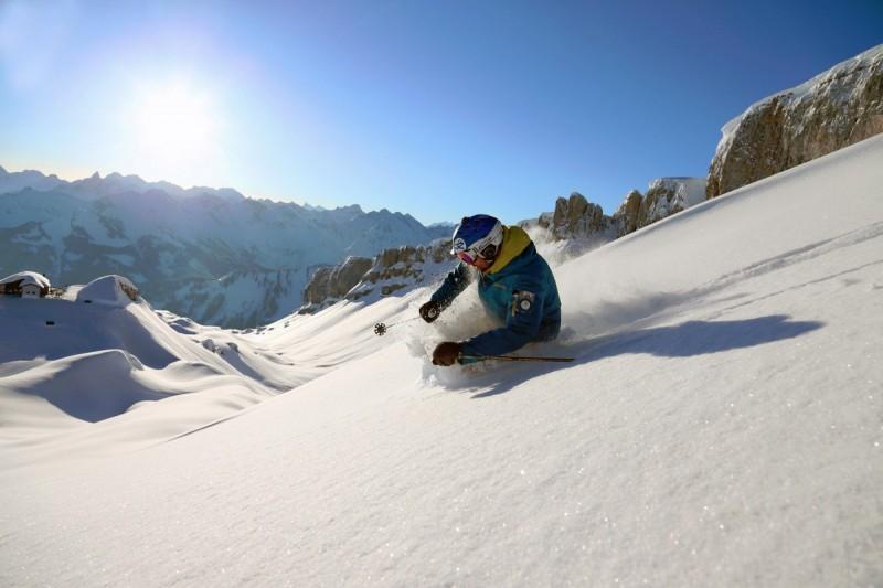 Zwei Skifahrer im Tiefschnee bei strahlendem Sonnenschein vor herrlichem Bergpanorama bei einem Fahrtechnikkurs im Gelände.