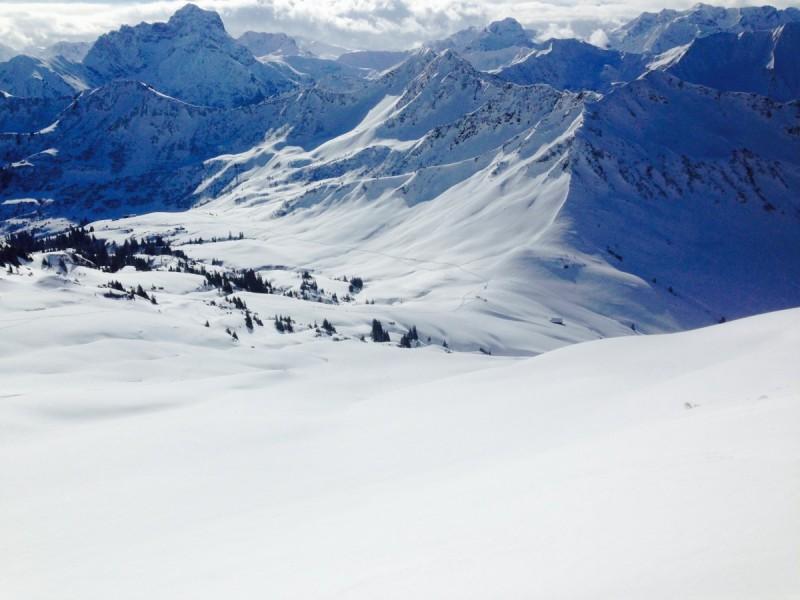 Skitourengeher mit den Skiern auf dem Rücken auf dem Weg zum Gipfel bei einem Fahrtechnikkurs im Gelände.