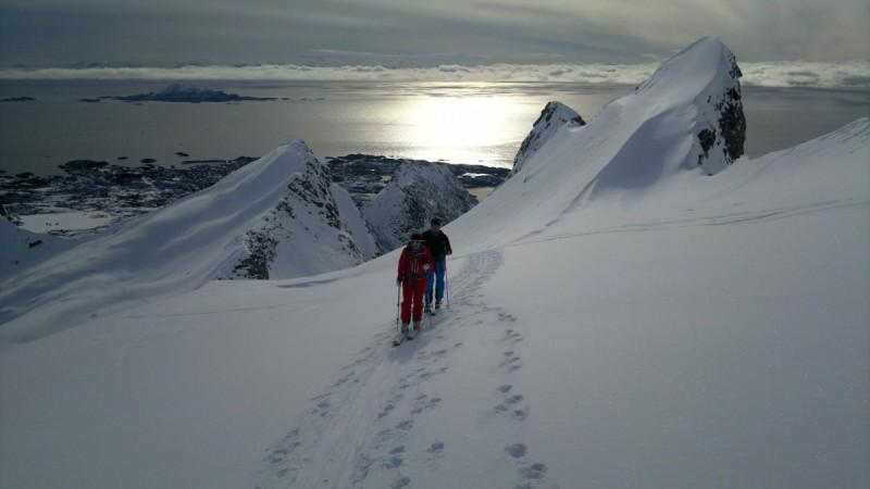 Mehrere Tourengeher sind mit ihren Ski auf dem Rücken auf dem Weg zum Gipfel bei der Skitourenreise Norwegen.