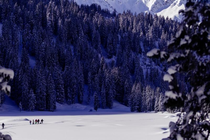 Schneeschuhwanderer sitzen in einer verschneiten Hütte.