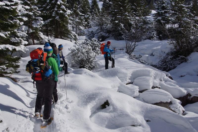 Schneeschuhwanderer sitzen in kleiner Hütte und blicken heraus.